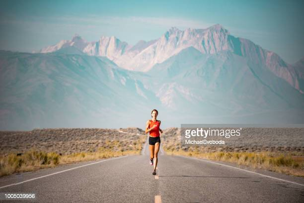 elite women athlete running up a road in the sierra mountains, california - endurance stock photos and pictures