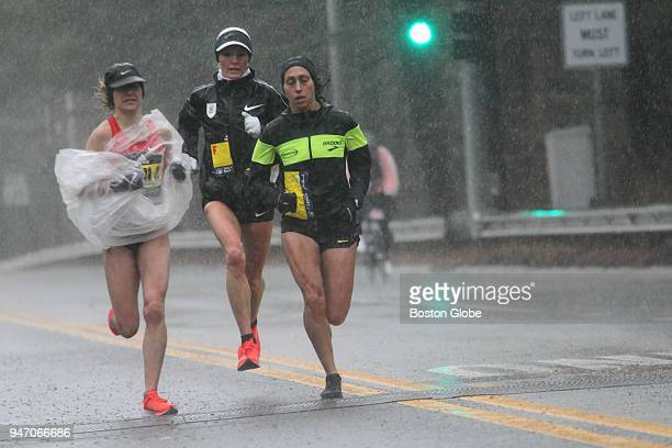 Elite women runners including Shalane Flanagan center and Desiree Linden right make their way through a downpour in Wellesley MA during the 2018...