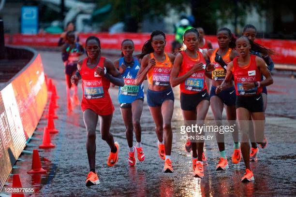 Elite women's pacemakers and leaders run in the rain early in the women's race of the 2020 London Marathon in central London on October 4 2020 This...
