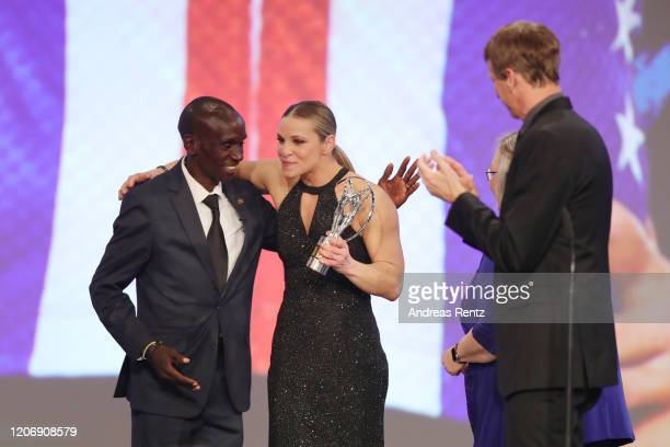 Eliud Kipchoge and Laureus Academy member Tony Hawk congratulate Laureus World Sportsperson of the Year with a Disability award winner US...