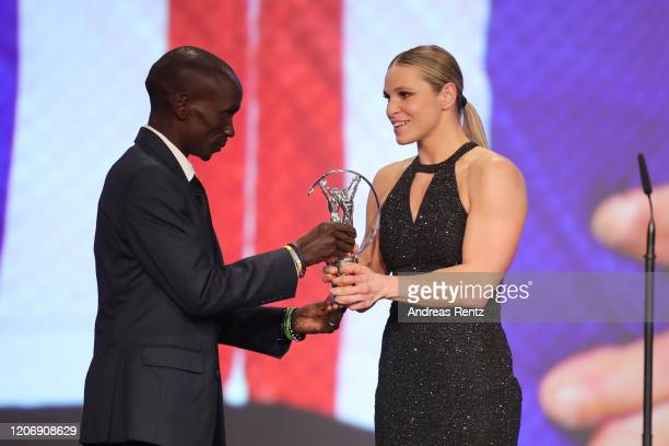 Eliud Kipchoge hands over the award to Laureus World Sportsperson of the Year with a Disability US crosscountry skier Oksana Masters during the 2020...