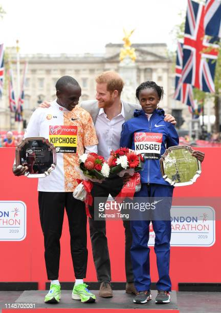 Eliud Kipchoge of Kenya and Brigid Kosgei of Kenya pose for a photo on the podium with Prince Harry Duke of Sussex after winning their respective...