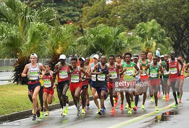 Eliud Kipchoge of Kenya and Callum Hawkins of Great Britain compete during the Men's Marathon on Day 16 of the Rio 2016 Olympic Games at Sambodromo...