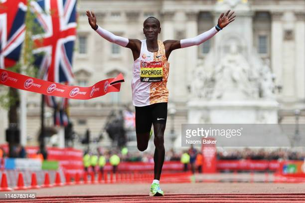 Eliud Kipchoge of Kenya crosses the finish line to win the Men's Elite race breaking the race record during the Virgin Money London Marathon at...