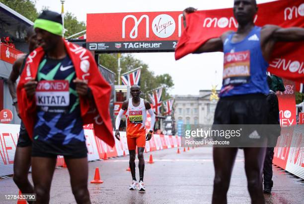 Eliud Kipchoge of Kenya reacts as he crosses the line as first place Shura Kitata of Ethiopia and second place Vincent Kipchumba of Kenya celebrate...