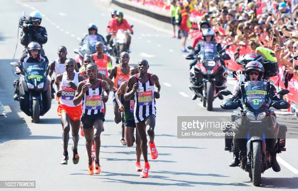 Eliud Kipchoge of Kenya tracks race leaders during the Elite mens race at Tower Bridge during the Virgin London Marathon on April 22 2018 in London