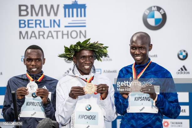 Eliud Kipchoge poses with Amos Kipruto and Wilson Kipsang all of Kenya during a podium ceremony after winning the Berlin Marathon 2018 in a new world...