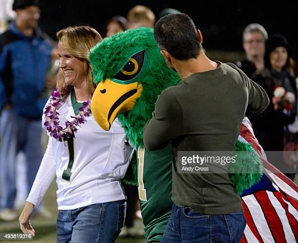 Elizabeth and Randall Mauro escort their son Cliff the Golden Eagle the Mountain Vista High School mascot on senior night before the Golden Eagles...