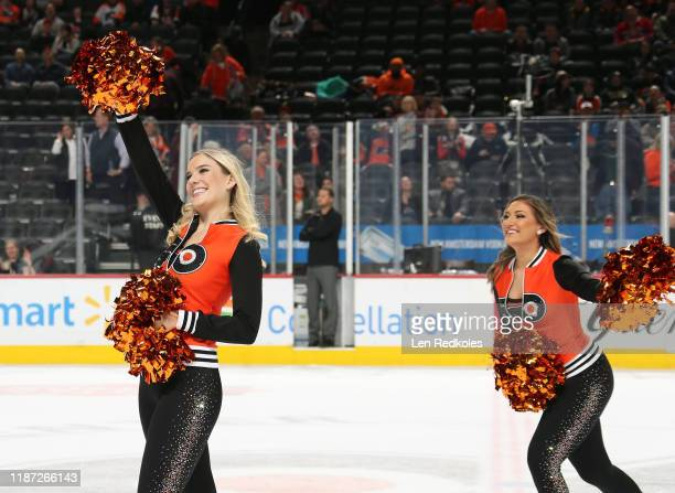 Elizabeth Ann Herman and Lexi Lord of the Philadelphia Flyers ice girls skate onto center ice during the first period intermission against the...