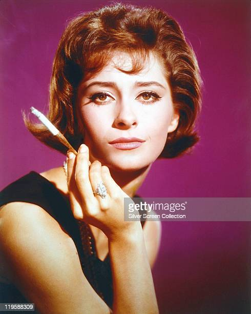 Elizabeth Ashley US actress poses with a lit cigarette held in a holder in a studio portrait against a purple background circa 1965