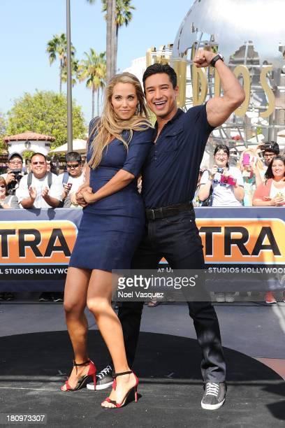 Elizabeth Berkley dances with Mario Lopez at Extra at Universal Studios Hollywood on September 18 2013 in Universal City California