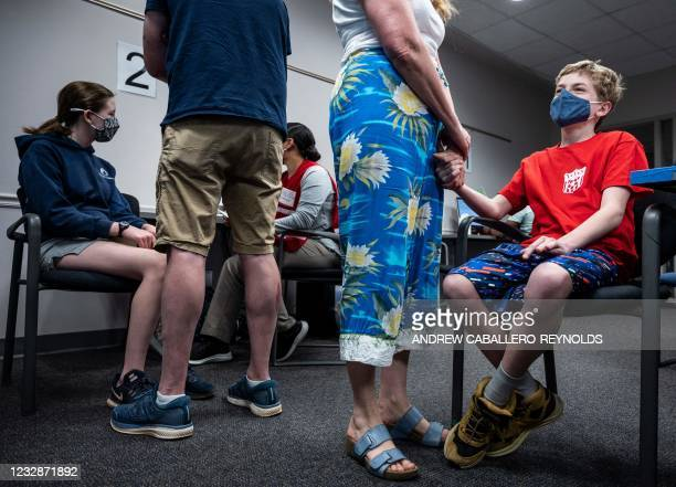 Elizabeth Brauer holds the hand of her son Luke Brauer as he waits to receive a Covid-19 vaccination at the Fairfax Government Center vaccination...