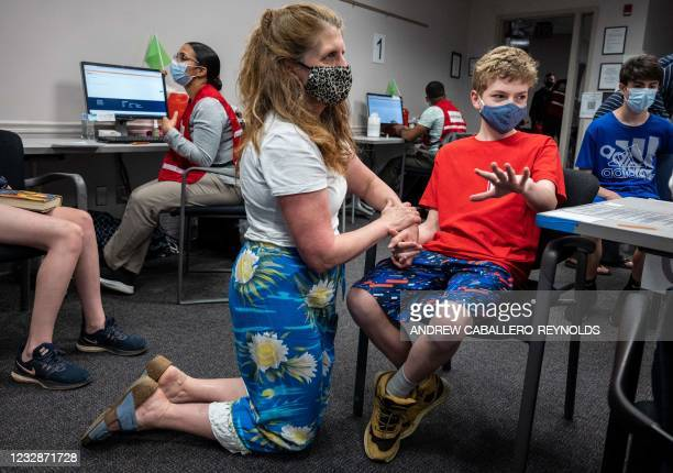 Elizabeth Brauer holds the hand of her son Luke Brauer before he receives a Covid-19 vaccination at the Fairfax Government Center vaccination clinic...