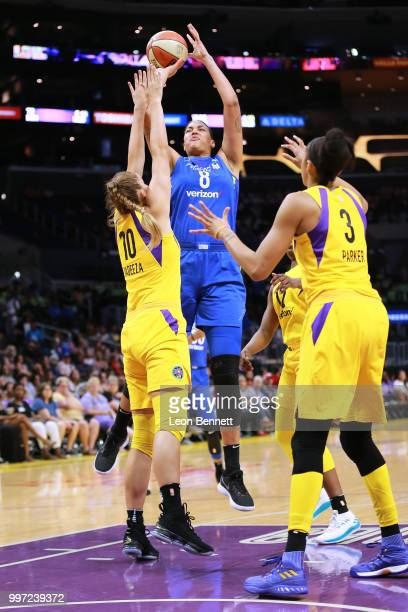 Elizabeth Cambage of the Dallas Wings handles the ball against Maria Vadeeva and Candace Parker of the Los Angeles Sparks during a WNBA basketball...