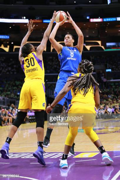 Elizabeth Cambage of the Dallas Wings handles the ball against Nneka Ogwumike and Chelsea Gray of the Los Angeles Sparks during a WNBA basketball...