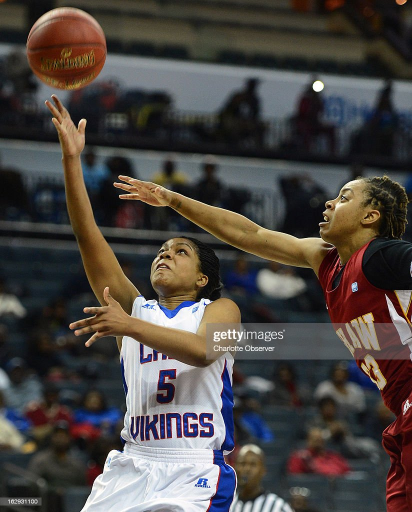 Elizabeth City State's Derricka Henry (5) drives to the basket as Shaw's Crystal Wilson applies defensive pressure during the CIAA tournament semifinals on Friday, March 1, 2013, at Time Warner Cable Arena in Charlotte, North Carolina. Shaw advanced, 76-61.