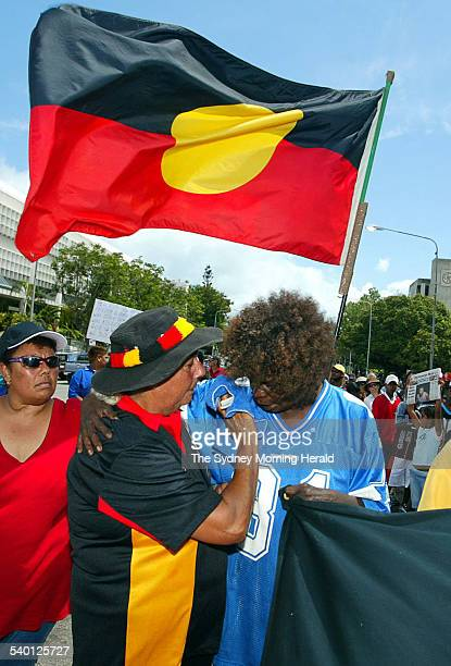 Elizabeth Doomadgee, the sister of Cameron Doomadgee, is comforted by friend Rinatta Pryor during a march through the streets of Townsville, North...