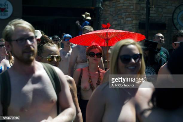 Elizabeth Gauss of Denver Colorado marches during the 2017 GoTopless Day Parade on August 26 2017 in Denver Colorado Founded in 2007 by the French...