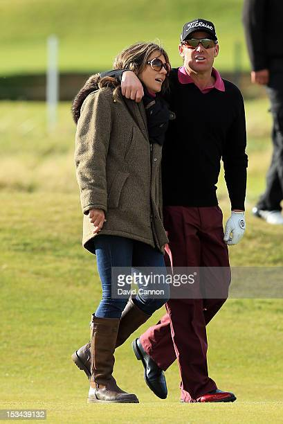 Elizabeth Hurley of England the actress with her fiancee the Australian Cricketer Shane Warne on the final hole during the second round of the Alfred...