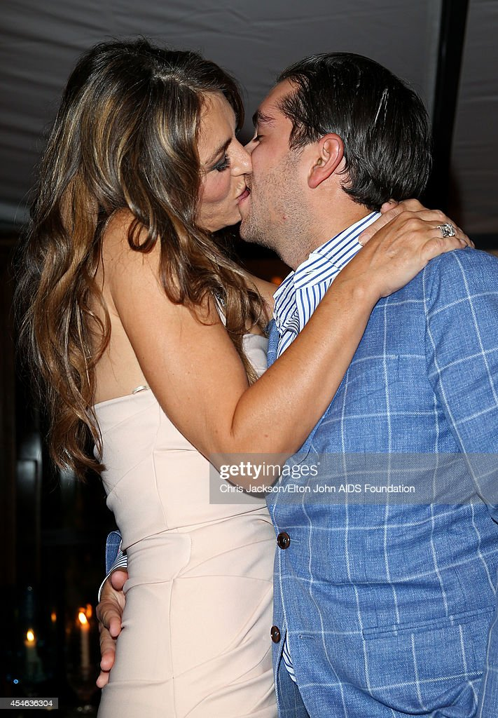 Elizabeth Hurley, wearing Chopard, kisses Julian Bharti after he paid 50,000 GBP to the Elton John AIDS Foundation in an auction during the Woodside End of Summer party to benefit the Elton John AIDS Foundation sponsored by Chopard and Grey Goose at Woodside on September 4, 2014 in Windsor, England. A percentage of revenue from the sale of this image will be donated to the Elton John AIDS Foundation. EJAF is one of the world's largest HIV grant-makers ejaf.org/London