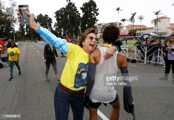 Elizabeth Hutton hugs Patrick Hutton after he finished in first place during the Synchrony Rock'n'Roll 5K Presented by Brooks on June 01 2019 in San...