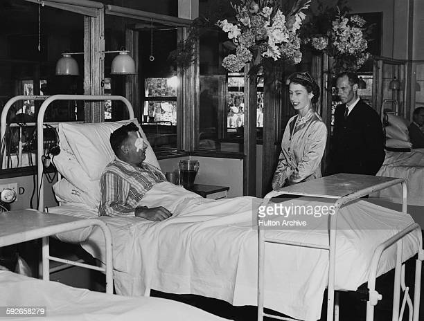 Elizabeth II talking to an injured exserviceman in bed during their visit to Repatriation General Hospital in Hobart circa 1954