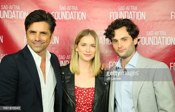 """Elizabeth Lail, Penn Badgley and John Stamos pose for a photo during a SAG-AFTRA Foundation Conversations - Screening of """"You"""" on October 11, 2018 in..."""
