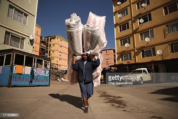 Elizabeth Maruatona carries a bundle of fabric with the US flag printed on it between apartment blocks in the Alexandra Township June 26 2013 in...