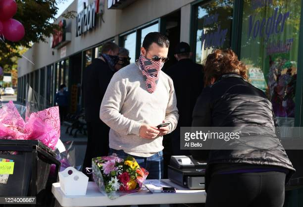 Elizabeth Mcginn works the cashier stand outside the Flowers by Voegler store on May 10 2020 in Merrick New York Theresa Soto is the owner of Flowers...