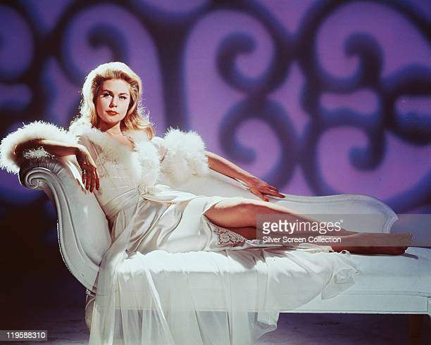 Elizabeth Montgomery US actress reclining on a white chaise longue wearing a white dressing gown trimmed with white fur circa 1965