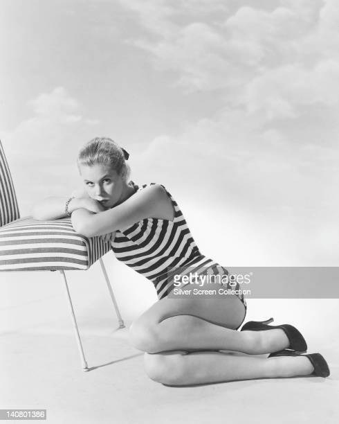 Elizabeth Montgomery US actress wearing a striped swimsuit as she sits on the ground resting her arms and head on the seat of a striped chair in a...