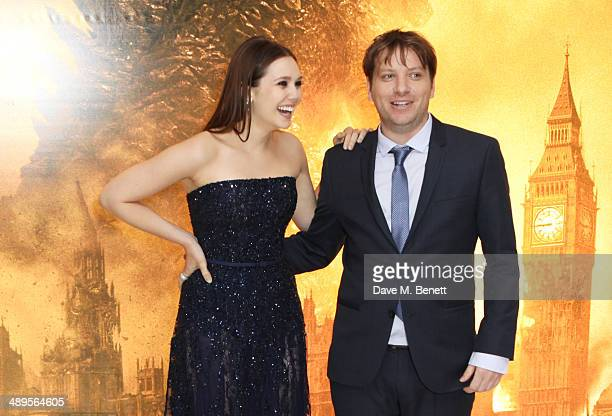 Elizabeth Olsen and director Gareth Edwards attend the European premiere of Godzilla at Odeon Leicester Square on May 11 2014 in London England