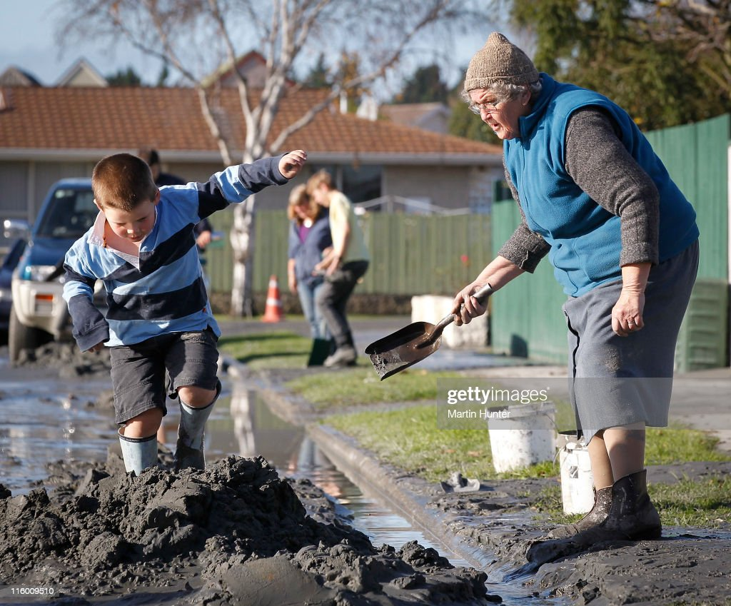 Elizabeth Parsons,73, of Shirley reacts as her grand son plays in a pile of liquefaction, the day after two magnitude 6.0 and 5.5 earthquakes struck the region on June 14, 2011 in Christchurch, New Zealand. The aftershocks have followed four months after the major earthquake which hit the city on February 22, 2011 resulting in the deaths of 181 people.