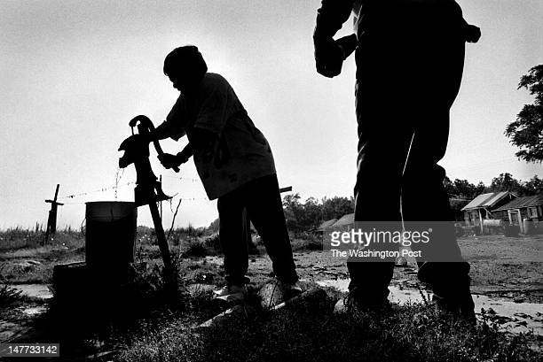 FILE Elizabeth Sample pumps water from a community well as neighbor Solomon Burton saunters up to chat in Bayview Virginia on May 9 1998 Although she...