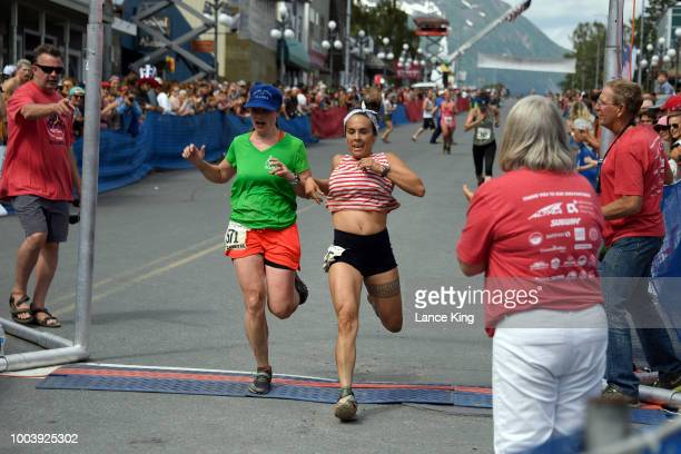 Elizabeth Saunders and Gwendolynn Stuart cross the finish line during the Women's Division of the 91st Running of the Mount Marathon Race on July 4...