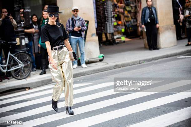 Elizabeth Sulcer, wearing a black t-shirt, gold pants, black boots and black hat, is seen outside the Giambattista Valli show during Paris Fashion...
