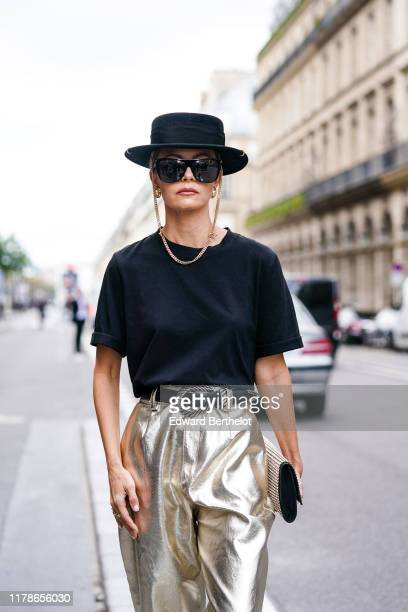 Elizabeth Sulcer wears a black hat earrings a black top a black belt a rhinestone studded bag shiny gold leather flowing pants outside Giambattista...