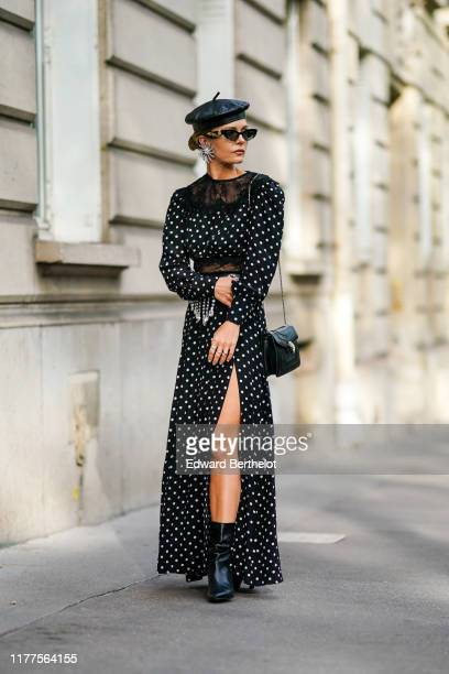 Elizabeth Sulcer wears earrings, a black leather beret hat, sunglasses, a black side-slit long dress with white polka dots, long sleeves and a black...