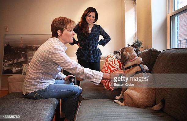 Elizabeth Swartz, left, of Westwood, dropped off 'Fenway,' a puggle, at Rachel Askew's apartment in the North End, Friday, September 12, 2014.