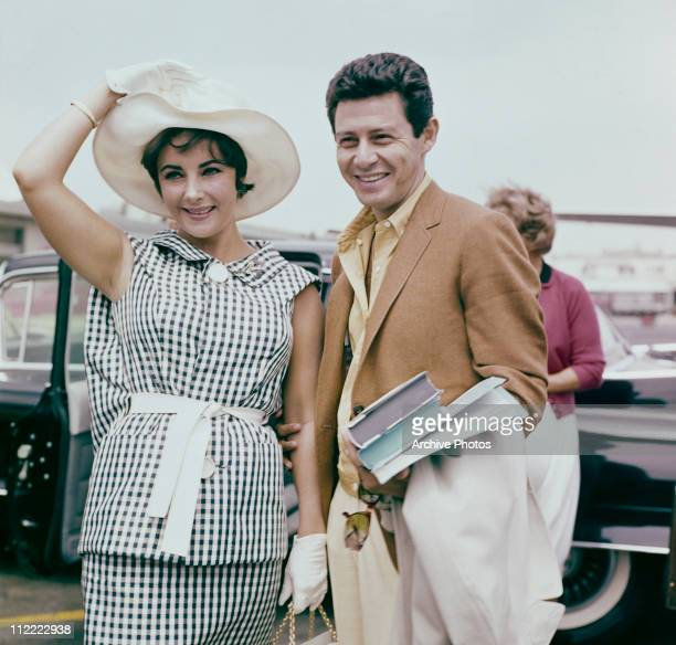 Elizabeth Taylor and Eddie Fisher, circa 1960. Taylor wears a black and white checked outfit with white wide brimmed hat and gloves.