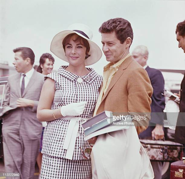 Elizabeth Taylor and Eddie Fisher circa 1960 Taylor wears a black and white checked outfit with white wide brimmed hat and gloves