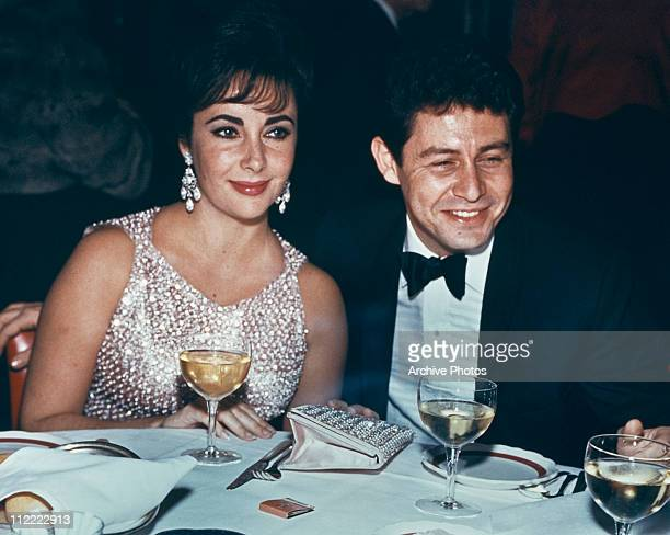 Elizabeth Taylor and Eddie Fisher dining at an event circa 1959 Taylor wears a silver beaded dress