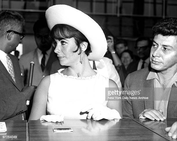 Elizabeth Taylor at Idlewild Airport just before taking off with her husband Eddie Fisher for Hollywood