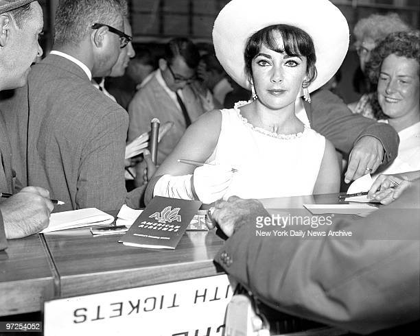 Elizabeth Taylor at Idlewild Airport signing autographs just before taking off with her husband Eddie Fisher for Hollywood