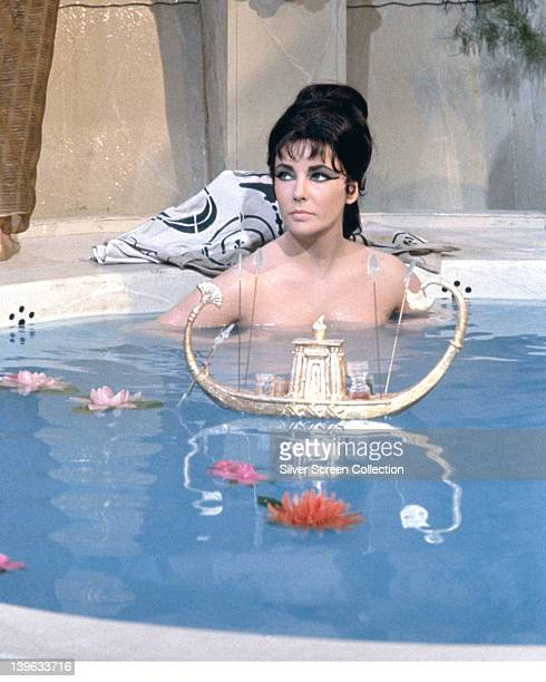 Elizabeth Taylor British actress bathing with a small boat and flowers floating on the water in a publicity still issued for the film 'Cleopatra'...