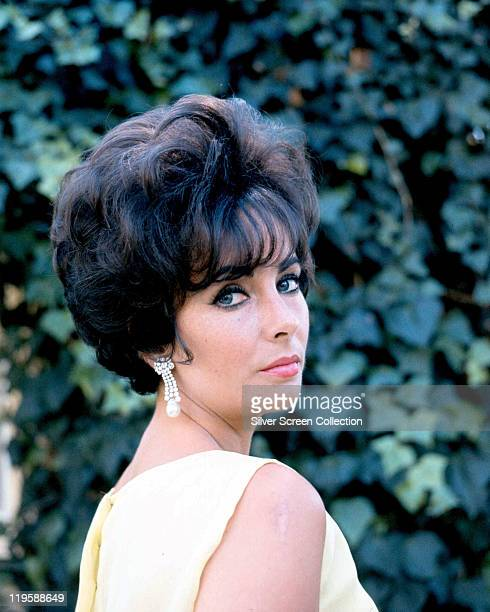Elizabeth Taylor , British actress, looking over her shoulder, against a background of ivy leaves, circa 1960.
