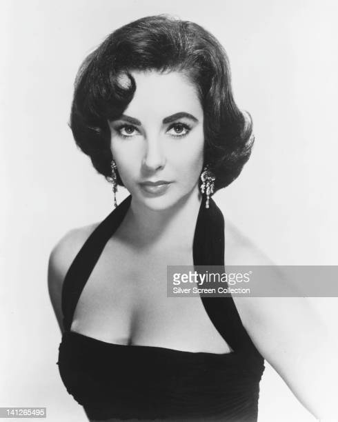 Elizabeth Taylor British actress wearing a black halterneck top and drop earrings looking glamorous in a studio portrait against a white background...