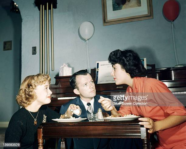 Elizabeth Taylor British actress wearing a coral coloured dress while dining with a man and woman circa 1960