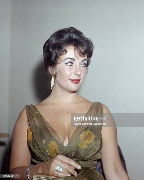 Elizabeth Taylor British actress wearing a green dress with floral motifs and a plunging neckline circa 1965