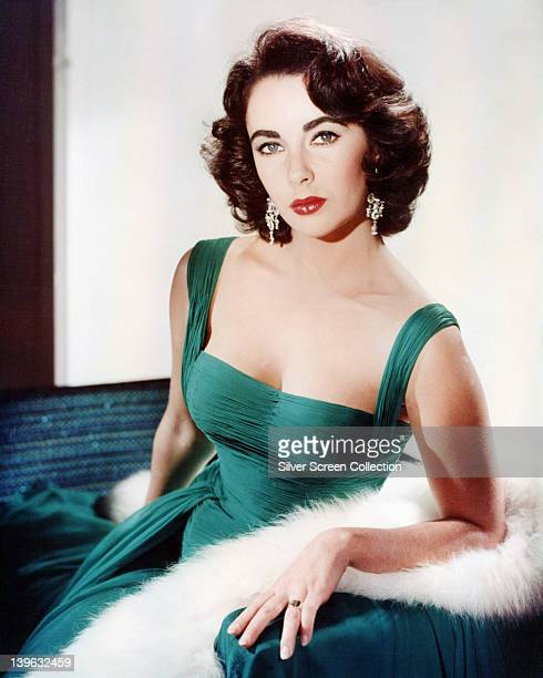 Elizabeth Taylor British actress wearing a green sleeveless lowcut dress with a white fur wrap on the arm of the armchair in which she sits circa 1950